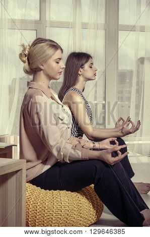 Two Girls Meditate In The Office After Work.