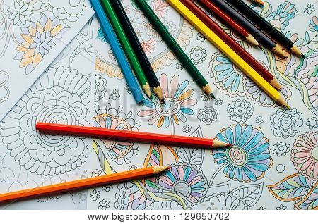 Image of woman coloring adult coloring book trend for stress relief. top view. colorer - antistress with colored pencils. Adult coloring books. The woman draws thereby relieves stress