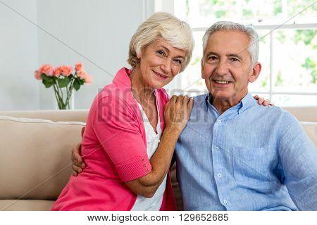Portrait of happy senior couple with arm around while sitting on sofa