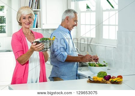 Portrait of smiling senior woman holding colander with man preparing vegetables in kitchen