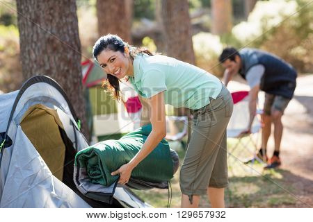 Woman smiling and holding a sleeping bag on a camp site