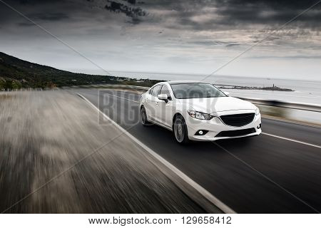 Anapa, Russia - September 7, 2014: Car Mazda drive on road at sea mountain cloudy sky landscape