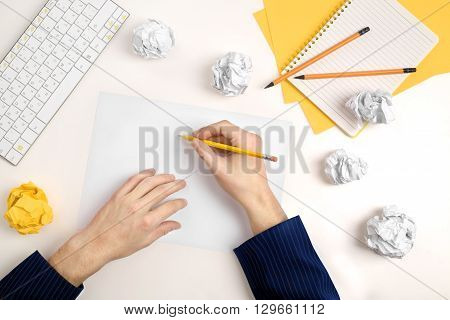 hands of a man thinking about idea with sheet of paper and pencil