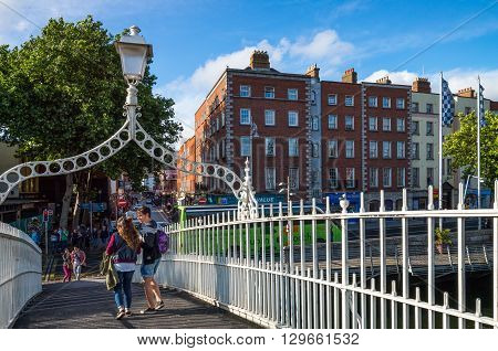 Dublin Ireland - July 31 2013: Young people on the Ha'penny bridge on the Liffey river Temple Bar district
