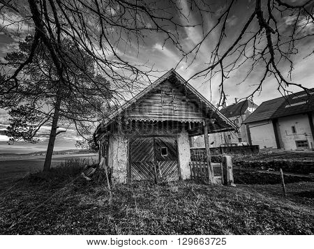 Small cottage surrounded with trees in the coutryside in black and white
