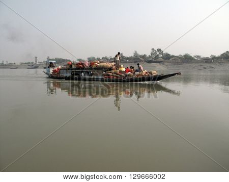 SUNDARBANS, INDIA - JANUARY 18: Wooden boat crosses the Ganges River January 18, 2009 in Sundarbans, West Bengal, India. To use a small wooden is easy, fast and cheap way how to cross the Ganges River