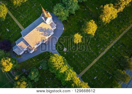Aerial view to churchyard - cemetery in Norway. Churchyard background. Graveyard photo taken from drone. Cemetery at sunset from the top. Cemetery with church