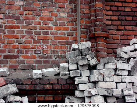 Pile of white silicate bricks near red brick wall as a background