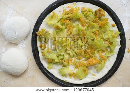 balls of dough pizza nearby at zucchini flowers pizza in a a baking tray