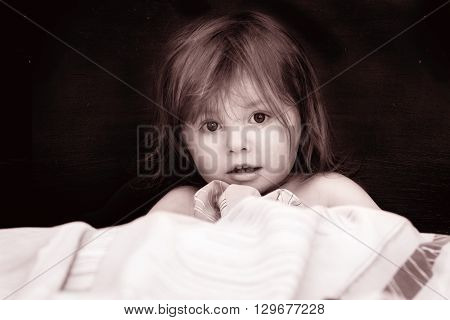 Little girl's portrait in a bed with a white cloth in black white tones