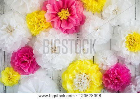 Paper handmade flowers isolated on white wood background. Beautiful floral background of white pink and yellow colors.