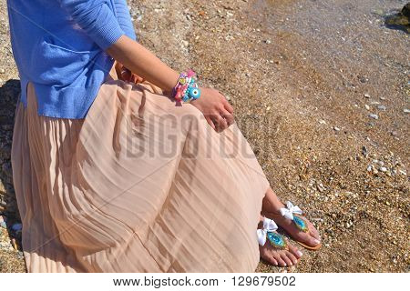 woman advertises traditional greek sandals and jewelry on beach