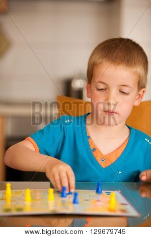 Young boy plays ludo game on a table in living room