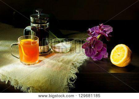still life tea with lemon purple orchid in dark colors