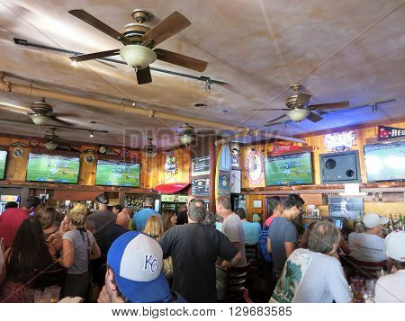 WAIKIKI OAHU - FEBRUARY 7: Crowd People watch Superbowl game at iconic Lulu's Bar. SupeBowl commercials cost roughly $3.8 million a piece taken February 7 2016 Waikiki Hawaii.