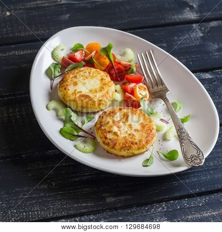 Potato cutlet and fresh tomato and celery salad on a light ceramic plate on dark wooden background.