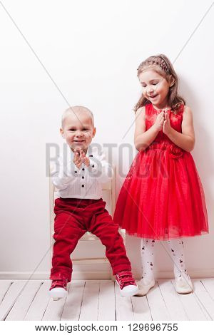 Little boy in red pants and a girl in a red dress posing for photos in harmony