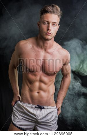 Lean athletic shirtless young man standing on dark background, with smoke around him