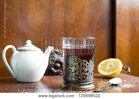 Cup of tea in antique glass-holder with sugar, lemon and teapot. Vintage concept. Horizontal view.