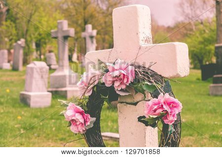 Funeral wreath with pink flower on a cross in a cemetary with a vintage filter. poster