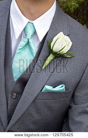man in suit with rose boutonniere on lapel with blue tie