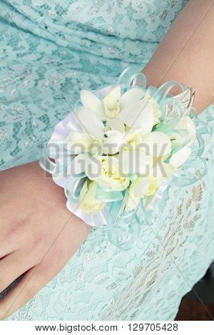 Corsage on female hand of blue ribbon and roses