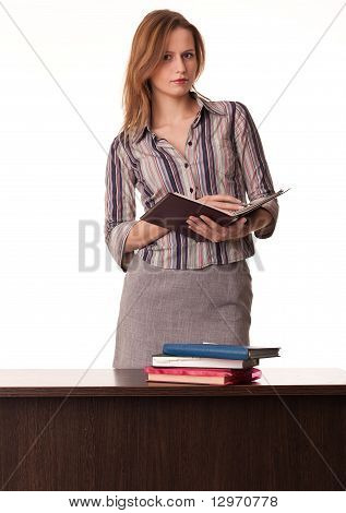 Confident Woman Teacher Holding Textbook Standing Behind The Desk