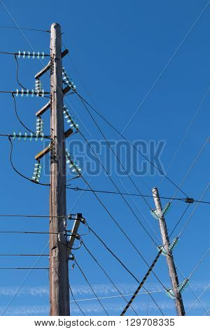 Powerlines with glass insulators against blue sky