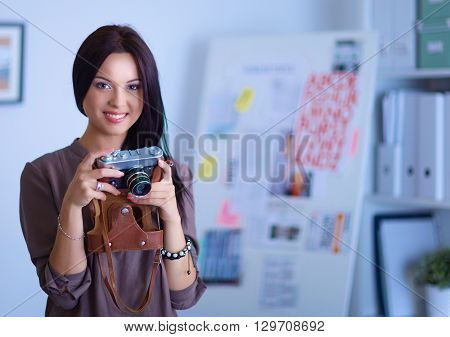 Pretty woman is a proffessional photographer with camera