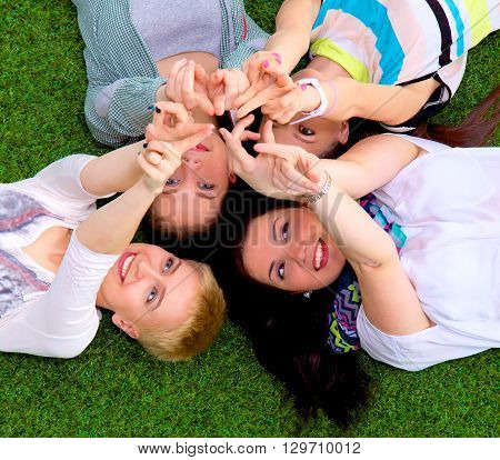 Group of friends with their hands in the ai. On the grass