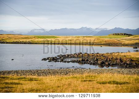 Lake yellow field and mountain landscape in winter of Southeast Iceland