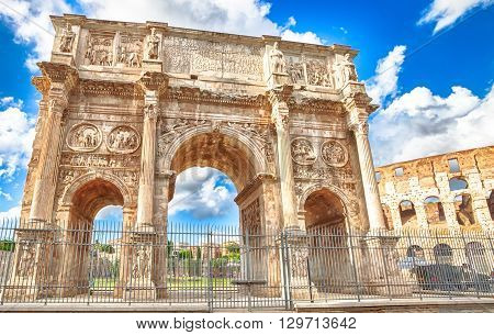 The spectacular Arch of Constantine, located between the Colosseum and the Arch of Titus, built to celebrate the triumph of the emperor Constantine in a sunny day. Rome, Lazio, Italy.
