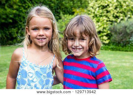 Portrait of happy siblings in back yard