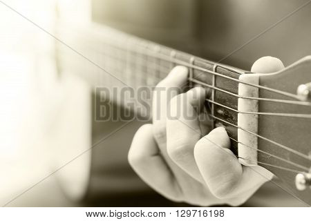 Woman's hands playing acoustic guitar with vintage filter, stock photo