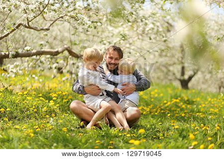 Happy Father Playing With His Young Children Outside On Spring Day