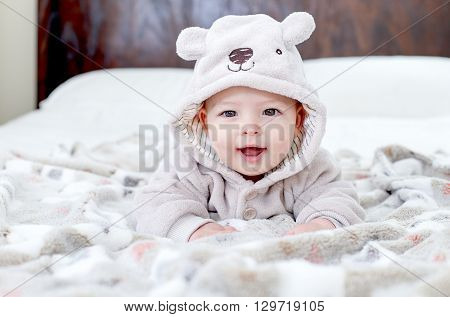 Baby boy wearing a bear outfit in white sunny bedroom on grey blanket. Newborn child relaxing on bed after bath or shower. Nursery for children. Textile and bedding for kids. New born kid with bear. New born kid during tummy time.