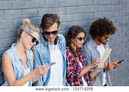 Friends in sunglasses leaning against wall using mobile phone and digital tablet