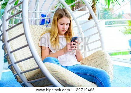 Blond Girl With Phone Sitting In Chair