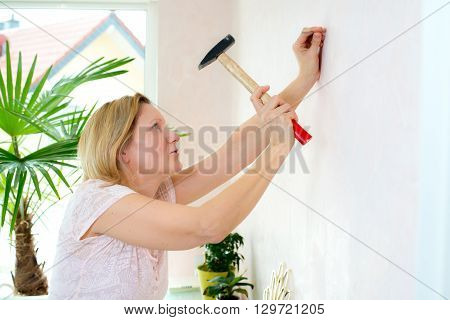 blond woman redecorate home and working with hammer