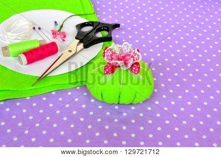 Felt pin cushion, idea for handmade crafts. Scissors, thread, needles, pins, paper templates - sewing kit