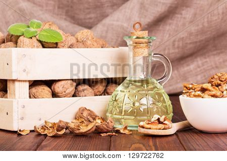 Walnut oil and nuts in a box on a background of burlap