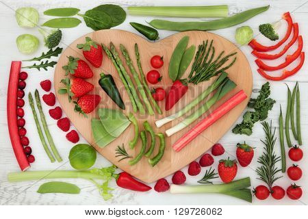 Health food with red and green vegetable and fruit selection on a heart shaped board over distressed white wood background. High in vitamins, antioxidants, minerals and anthocyanins.