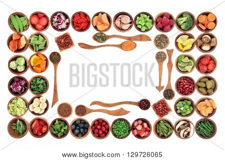 Paleo diet health and super food of fruit, herbs, vegetables, nuts and seeds in wooden bowls forming an abstract border over white background. High in vitamins, antioxidants and anthocyanins.