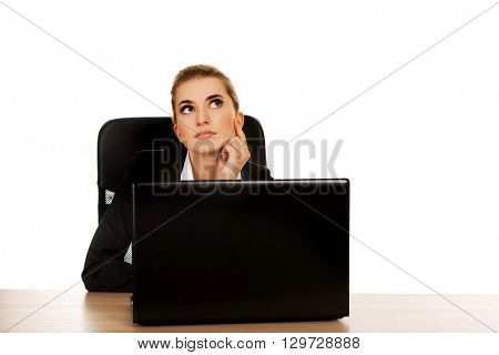 Young businesswoman behind the desk, using laptop