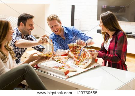 Happy young people eating pizza in the apartment