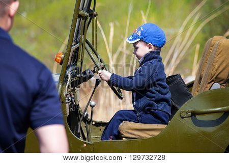 KHABAROVSK RUSSIA - MAY 14 2016: Little boy sitting in old Willys MB and his father is looking to him