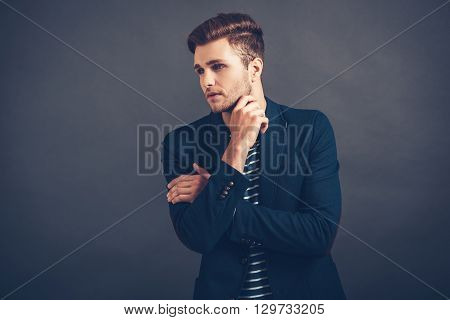 Cool and calm. Confident young handsome man keeping hand on chin and looking away while standing against grey background
