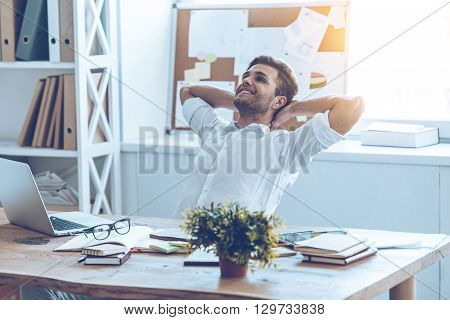 Great job. Cheerful young handsome man keeping hands behind his head and looking away with smile while sitting at his working place