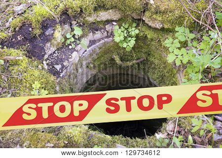"""Close view of yellow and red plastic caution or restriction tape """"STOP"""" preventing from entering to the hole"""
