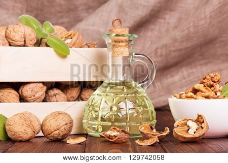 The box with walnuts and butter, and a carafe of them on an abstract brown background